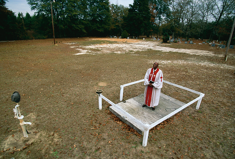 A Southern Baptist preacher inspects of the ruins of his church, destroyed by arson.