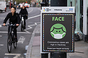 As Londoners await the second coronavirus national lockdown people out and about, some wearing face masks and some not, pass advice boards in Hackney before a month-long total lockdown in the UK on 2nd November 2020 in London, United Kingdom. The three tier system in the UK has not worked sufficiently, to suppress the virus, and there have have been calls by politicians for a 'circuit breaker' complete lockdown to be announced to help the growing spread of the Covid-19.