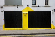A yellow triangle on the side of a closed business in central London is matched by a smaller version on the far left warning of wet paint. Double-yellow no parking lines are on the road at the bottom. It appears the business here is either closed or soon to reopen given the fresh paint. It is an urban sign or geometric shapes - large black square and rectangle plus the triangle.