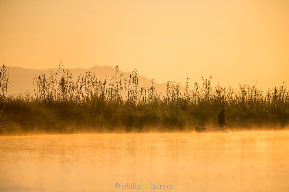 Man in canoe at sunrise on lower Zambezi River in Zambia