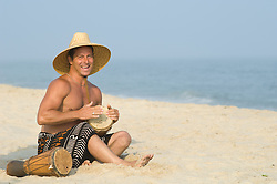 Playful Man in a straw hat sitting on the beach playing bongo drums