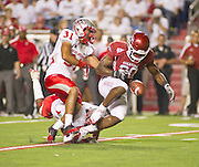 Sep 10, 2011; Little Rock, AR, USA; Arkansas Razorback running back Ronnie Wingo Jr. (20) fumbles the ball as New Mexico Lobos defensive back Daunte Caro (31) makes the tackle during the second half of a game at War Memorial Stadium.  Mandatory Credit: Beth Hall-US PRESSWIRE