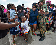 Royal Bahamas Defense Forces and Royal Bahamas Police help evacuees move to an awaiting ferry boat at Marsh Harbour Port in Abaco on Friday, September 6, 2019