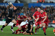 Kieron Fonotia of the Ospreys ©, despite being surrounded by Scarlets players gets his pass away to teammate Jeff Hassler (l).  Guinness Pro14 rugby match, Ospreys v Scarlets at the Liberty Stadium in Swansea, South Wales on Saturday October 7th 2017. <br /> pic by Andrew Orchard, Andrew Orchard sports photography.