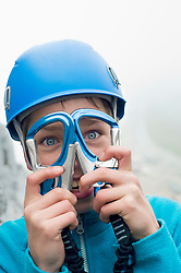 Young teenage boy holding two climbing Carabiner