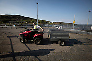 Islander Seamus McNeill preparing for the arrival of the Caledonian MacBrayne ferry at Scalasaig from Oban on the the Inner Hebridean island of Colonsay on Scotland's west coast.  The island is in the council area of Argyll and Bute and has an area of 4,074 hectares (15.7 sq mi). Aligned on a south-west to north-east axis, it measures 8 miles (13 km) in length and reaches 3 miles (4.8 km) at its widest point, in 2019 it had a permanent population of 136 adults and children.