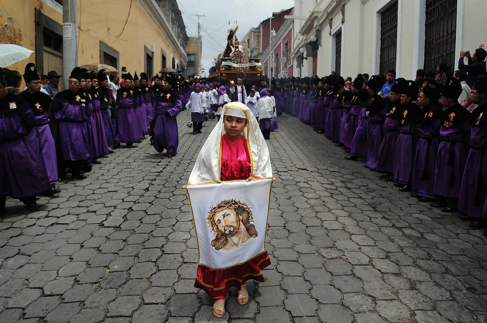 """Apr 22, 2011 - Quetzaltenago, Guatemala - Semana Santa or Holy Week continued in Quetzaltenago with the """"Procession to the Cathedral"""" Resident of the second largest city in Guatemala lined the streets of the Procession route leading into the Central Park. A young girl dressed as the Virgin Mary carries an image of Jesus Christ as she walks down the Procession Route Friday Morning..(Credit Image: © Josh Bachman/ZUMA Press)"""