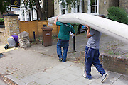 Two delivery workmen carry a heavy roll of carpet along a south London street.