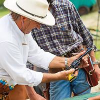 Competitor unloads his weapon during the Cowboy Action Shooting European Championship in Dabas, Hungary on August 11, 2012. ATTILA VOLGYI