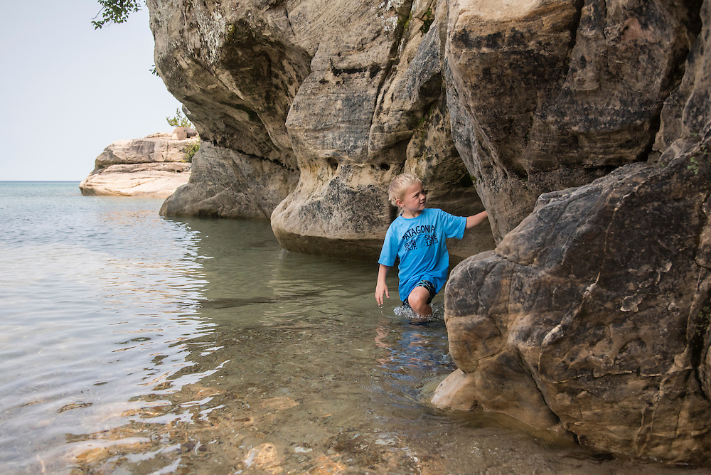 Children explore a small sea cave at The Coves area of Pictured Rocks National Lakeshore of Munising, Michigan.