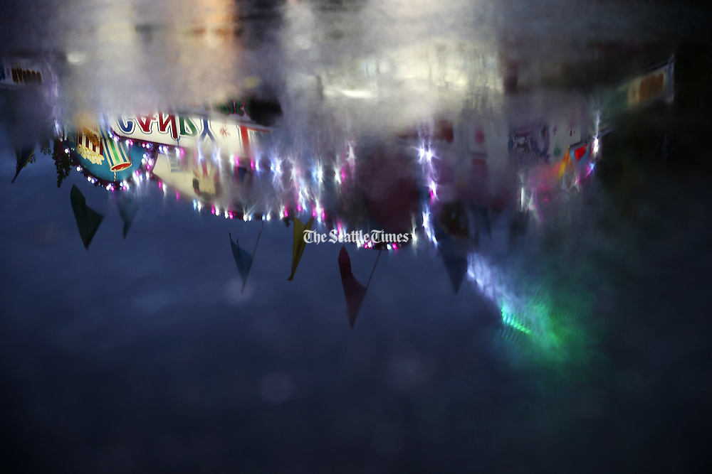 A reflection of a food kiosk is reflected in the water at the Evergreen State Fair Tuesday, Sept. 1, 2015. (Erika Schultz/The Seattle Times)
