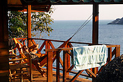 A traveler enjoys an afternoon siesta in a hammock at the origin beach huts. Hat Yuan Beach, Koh Phangnan, Thailand