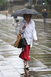 © Licensed to London News Pictures. 22/08/2016. Leeds, UK. A woman shelters under an umbrella on a rainy and windy day in Leeds, West Yorkshire. Forecaster are predicting a heatwave this week, but it has started with rain, wind and no sunshine. Photo credit : Ian Hinchliffe/LNP