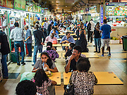 "27 DECEMBER 2015 - SINGAPORE, SINGAPORE:  People eat at the ""Hawker Stalls"" in Tekka Market. First opened in 1915, the market was moved to its present location in 1982 and renovated in 2009. It is one of the most famous hawker stall (street food) areas in Singapore. Singapore moved the street food carts the city was famous for into markets and malls and created ""Hawker Stalls.""     PHOTO BY JACK KURTZ"