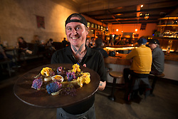 Chef Nathan Berrigan-Dunlop holds a poached cauliflower dish -- with leek confit, soft cooked egg and ruby mustard greens -- at the Starline Social Club in Oakland, Calif., Wednesday, Feb. 1, 2017. (Photo by D. Ross Cameron)