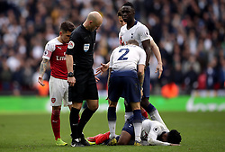 Tottenham Hotspur's Danny Rose lies injured as Arsenal's Lucas Torreira looks on before being shown a red card by referee Anthony Taylor during the Premier League match at Wembley Stadium, London.