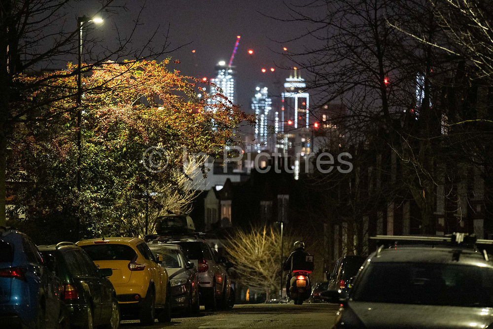 The glow of distant buildings overlooks a passing scooter rider and parked cars in a dark residential street in Herne Hill, south London on 21st January 2021, in London, England.