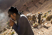 A Berber man lights his cigarette as he travels with a mule train over Tizi n'Rougoult Pass in the M'Goun Massif, Central High Atlas, Morocco.