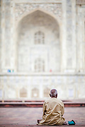 A man sitting in the courtyard outside the main, ivory-white marble mausoleum building, Taj Mahal, Agra, India