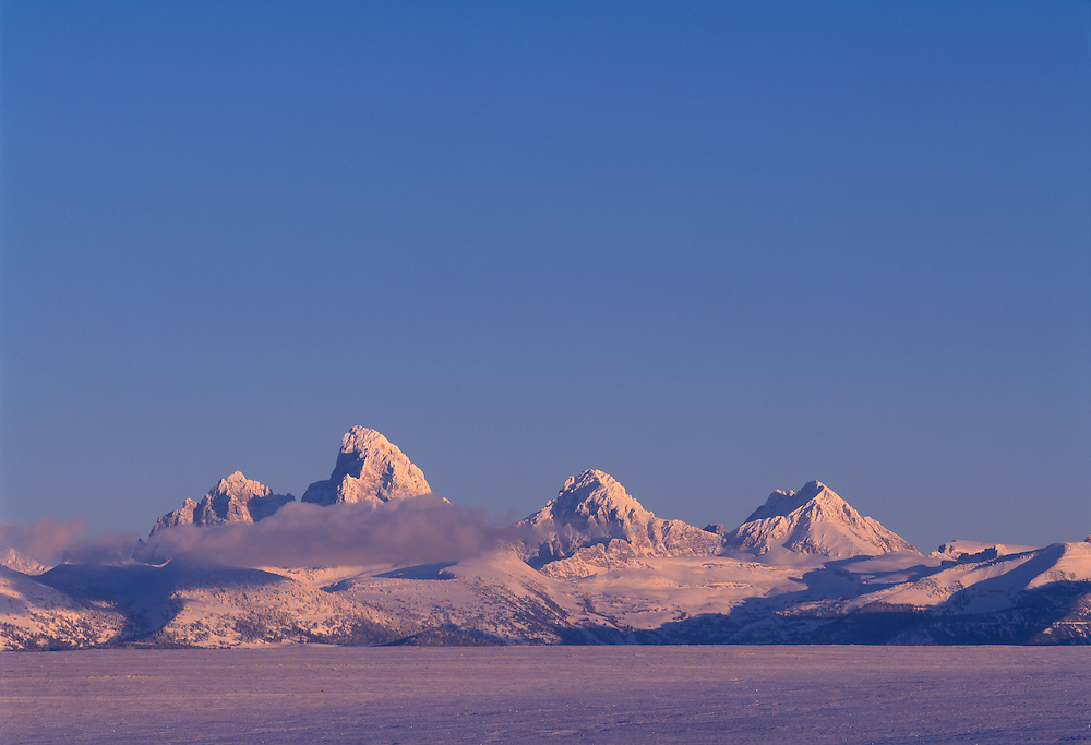 The Teton Mountain Range just outside Driggs Idaho as seen from the Idaho Side of Grand Targhee National Forest with the tallest peak the Grand Teton at 13,770 ft (4,197 m) seen on cold winter Alpenglow evening