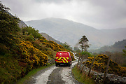 A red post office delivery van driving down Greenside Road, back down the valley to the village of Glenridding on the shore of Lake Ullswater, The Lake District, United Kingdom.