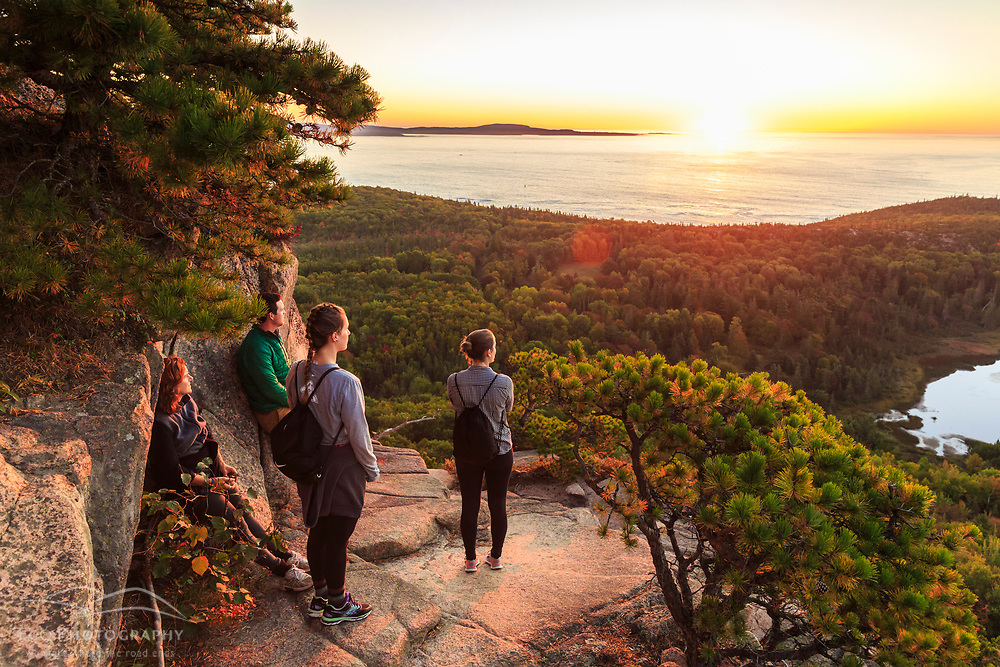 """Hikers watch the sunrise from a ledge on """"The Beehive"""" in fall in Maine's Acadia National Park."""