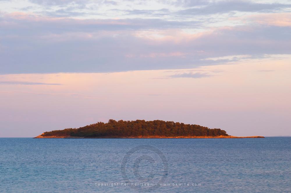 View across the sea towards an island off the Korcula island at sunset. Prizba village. Korcula Island. Prizba, Riva Apartments, Danny Franulovic. Korcula Island. Dalmatian Coast, Croatia, Europe.