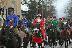© Licensed to London News Pictures. 24/12/2014.  The King's Troop Royal Horse Artillery have delighted onlookers this morning by donning Christmas gear as they rode out. The troop left their barracks in Woolwich and trotted through South East London streets on the way to Morden College in Blackheath where local people were able to see them up close as mulled wine and mince pies were served. The event has become a new Christmas tradition since the Troop moved to purpose built barracks in Woolwich in February 2012. Credit : Rob Powell/LNP