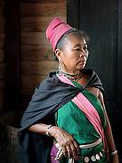 Portrait of a Kayah ethnic minority woman on 22nd March 2016 in Kayah State, Myanmar. Myanmar is one of the most ethnically diverse countries in Southeast Asia with 135 different indigenous ethnic groups with over a dozen ethnic Karenni subgroups in the Kayah region. Kayah women wear a simple tunic worn with a broad white sash decorated with coloured tassles and a striped hand-woven head-cloth