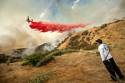 September 2, 2017 - Burbank, California, U.S. - Aaron Funk waters down the hillside behind his parents' home as a plane makes a drop near Petaluma Dr. in Sun Valley. A raging brush fire in the Verdugo Mountains that began Friday afternoon has consumed over 5,000 acres and destroyed three structures as it continues to threaten homes in Burbank and Glendale Saturday evening. (Credit Image: © Paul Rodriguez/The Orange County Register via ZUMA Wire)