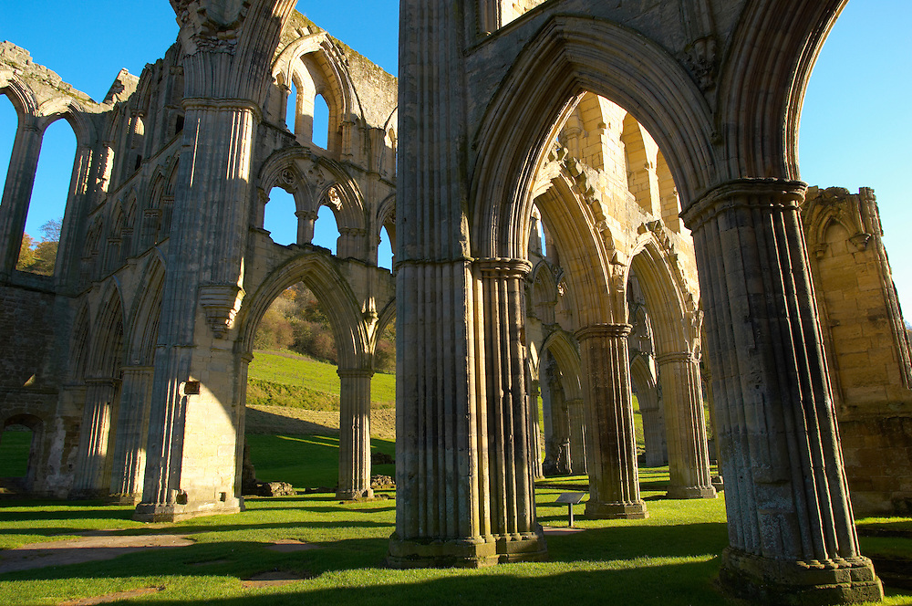 Rievaulx Abbey main aisle arches and windows. North Yorkshire, England . Rievaulx Abbey was a Cistercian abbey in Rievaulx, situated near Helmsley in the North York Moors National Park, North Yorkshire, England. Rievaulx Abbey was one of the great abbeys in England until it was seized under Henry VIII of England in 1538 during the dissolution of the monasteries. Founded in 1132 by twelve monks from Clairvaux Abbey. Rievaulx Abbey remote location was well suited to the order's ideal of a strict life of prayer and self-sufficiency with little contact with the outside world. <br /> <br /> Visit our MEDIEVAL PHOTO COLLECTIONS for more   photos  to download or buy as prints https://funkystock.photoshelter.com/gallery-collection/Medieval-Middle-Ages-Historic-Places-Arcaeological-Sites-Pictures-Images-of/C0000B5ZA54_WD0s