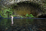 Hamilton Boyce wades across Eagle Creek below a basalt arch, Columbia River Gorge National Scenic Area, Oregon.