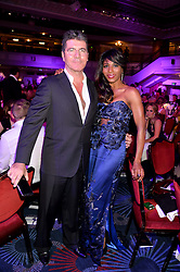 SIMON COWELL and SINITTA at the Caudwell Children's annual Butterfly Ball held at The Grosvenor House Hotel, Park Lane, London on 15th May 2014.