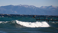 Brennan Lagasse hops into an empty lineup off a pier on Tahoe's West Shore. A frigid east wind creates a rare swell near Homewood, CA.