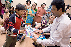 Boy being presented with a prize during the celebration of Navratri; the Hindu festival of Nine Nights,