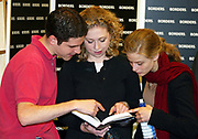 Chelsea Clinton looks at her mothers book with two friends during Hilary's book signing session at Borders, Oxford.