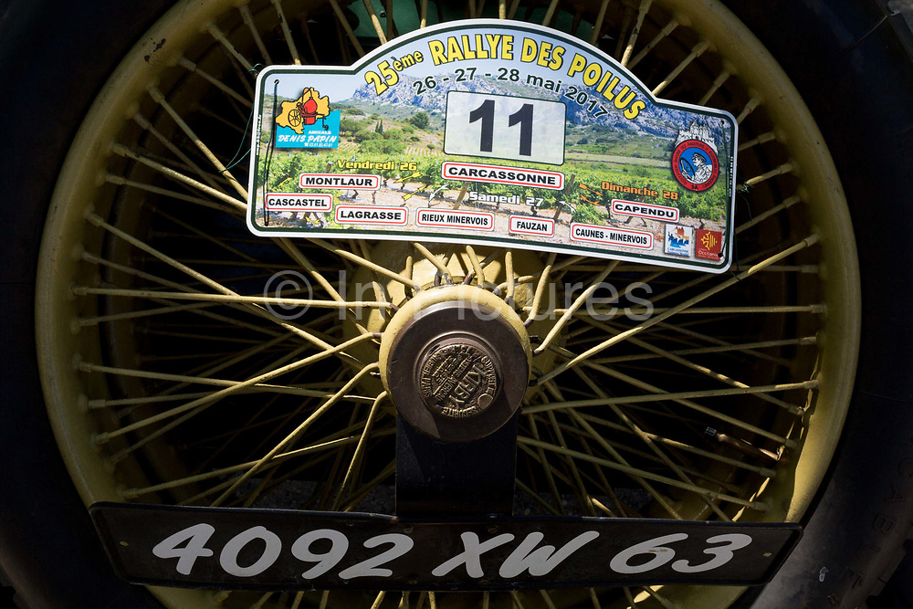 Detail of a rear wheel from a visiting vintage car in the centre of a French village, during a three-day rally journey through the Corbieres wine region, on 26th May, 2017, in Lagrasse, Languedoc-Rousillon, south of France. Lagrasse is listed as one of Frances most beautiful villages and lies on the famous Route 20 wine route in the Basses-Corbieres region dating to the 13th century.