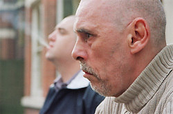 Portrait of two male residents sitting outside homeless hostel for people with learning difficulties,