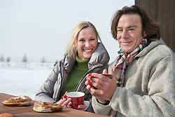 Portrait of couple having tea and snack, smiling, Bavaria, Germany