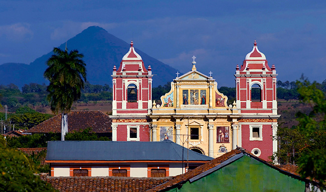 Brightly colored 18th century El Calvario Church rises above central Leon, and the very active Cerro Nego Volcano looms behind.