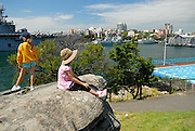 Two children (10 years old, 6 years old) looking across Woolloomoolo Bay to Garden Island Naval Base, and the Andrew (Boy) Charlton Swimming Pool. The Domain, Sydney, Australia