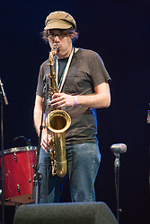 Member of Youngblood Brass Band playing a saxophone on stage at the WOMAD (World of Music; Arts and Dance) Festival in reading; 2005,