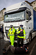 A truck drivers tries to blockade a lorry leaving the port as tensions are high between police and drivers who have been waiting over 48 hours for the Port of Dover to re-open, on the 23rd of December 2020, Dover, Kent, United Kingdom. The French border was closed due to a new strain of COVID-19 all travellers are now waiting to receive a COVID-19 test before they can board a ferry to Calais, France. Dover is the nearest port to France with just 34 kilometres (21 miles) between them. It is one of the busiest ports in the world. As well as freight container ships it is also the main port for P&O and DFDS Seaways ferries.  (photo by Andrew Aitchison / In pictures via Getty Images)