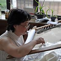 Asia, China, Suzhou. Chinese silk embroiderer.