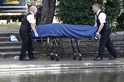 © Licensed to London News Pictures. 13/08/2019. London, UK. Police remove a body from a pond in Feltham, south west London after it was seen by members of the public. A man thought to be aged 54 was pronounced dead at the scene at 10: 15. A cordon remains in place. Photo credit: Peter Macdiarmid/LNP