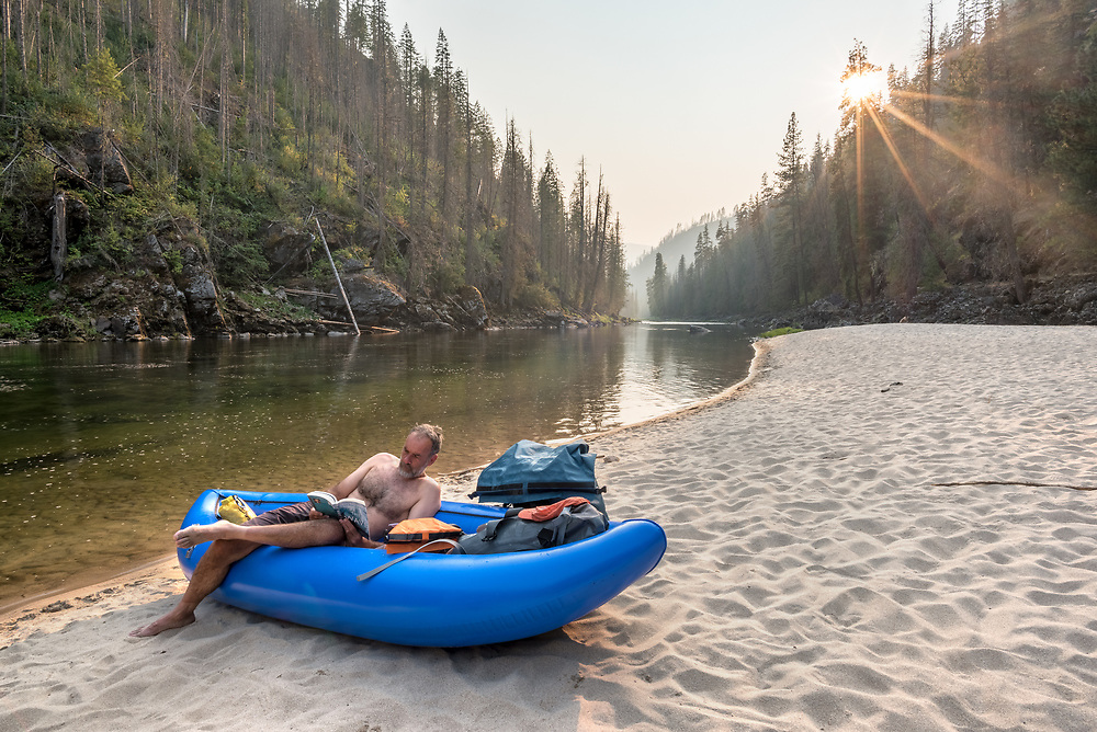 River runner reading and relaxing in an inflatable kayak on a beach along Idaho's Selway River.