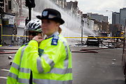 Police lines protect burnt out remains of a row of shops and flats on London Road in Croydon. The day after rioting took place in Croydon in South London. Riots flared for a third night in a row, resulting in burnt out buildings, looted shops and general smashed up devastation.