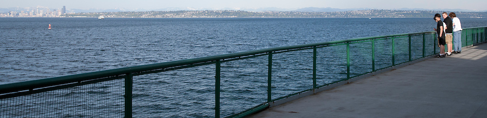 Three young men stand at the railing of a Washington State Ferry on a crossing of Puget Sound with Seattle, Washington in the background panorama