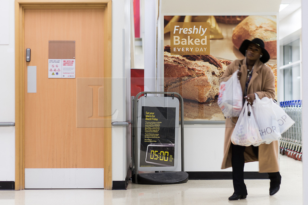© Licensed to London News Pictures . 26/11/2015 . Manchester , UK . A woman with shopping bags walks past a sign advertising Black Friday at a branch of Tesco in Salford this evening (Thursday 26th November) as Tesco branches are due to close for five hours ahead of Black Friday sales starting at 5am on Friday 27th November 2015 . Last year (2014) scuffles and fights were reported amongst queueing bargain-hunters . Photo credit: Joel Goodman/LNP