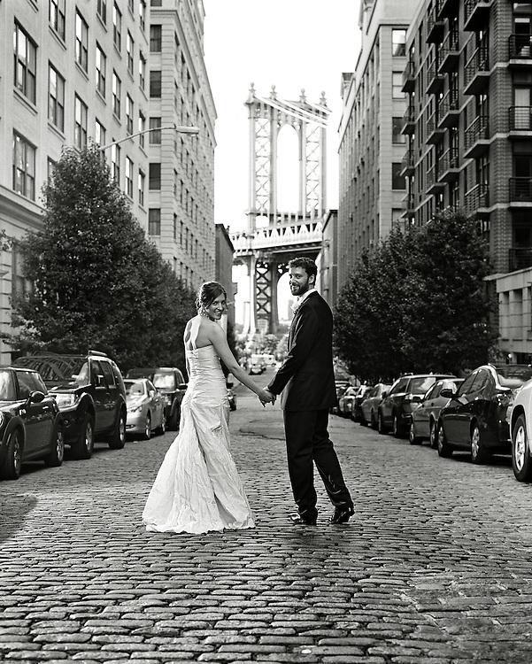 Black & White photo of Bride and Groom walking down cobblestone Brooklyn NY street with Manhattan Bridge in background